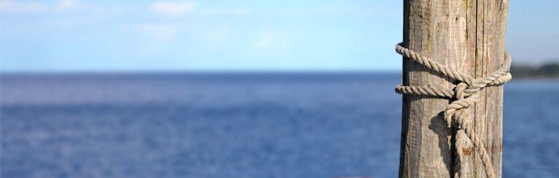 Foto: Pfahl mit Tau im Wasser