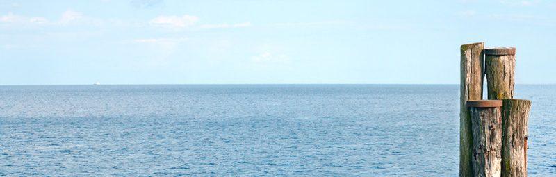 Foto: Vier Pfähle im Wasser